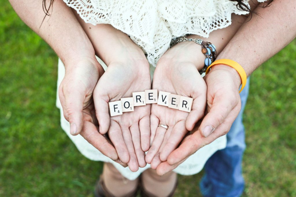 couple holding scrabble pieces that spell out the word 'forever' which is what online couple therapy can help the couple achieve