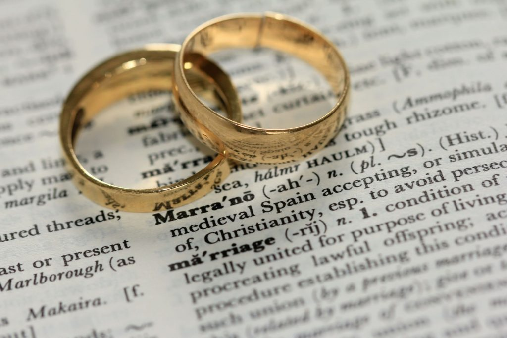 wedding rings on top of a page in a dictionary with the word 'marriage'. Online couple therapy can lead to a happy marriage